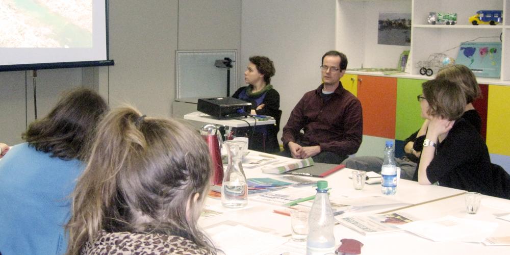 Mehrere Teilnehmer an einer Veranstaltung sitzen an einem Tisch und diskutieren.