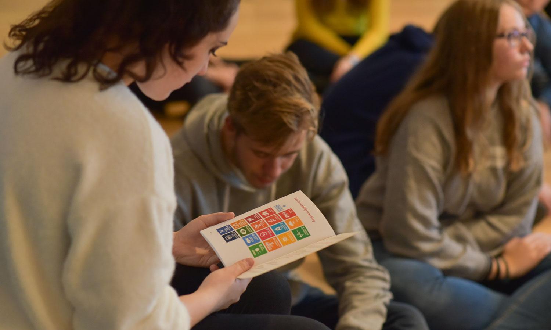 Schüler der Sekundarstufe im Unterricht, die Schülerin im Vordergrund liest in einer Infobroschüre